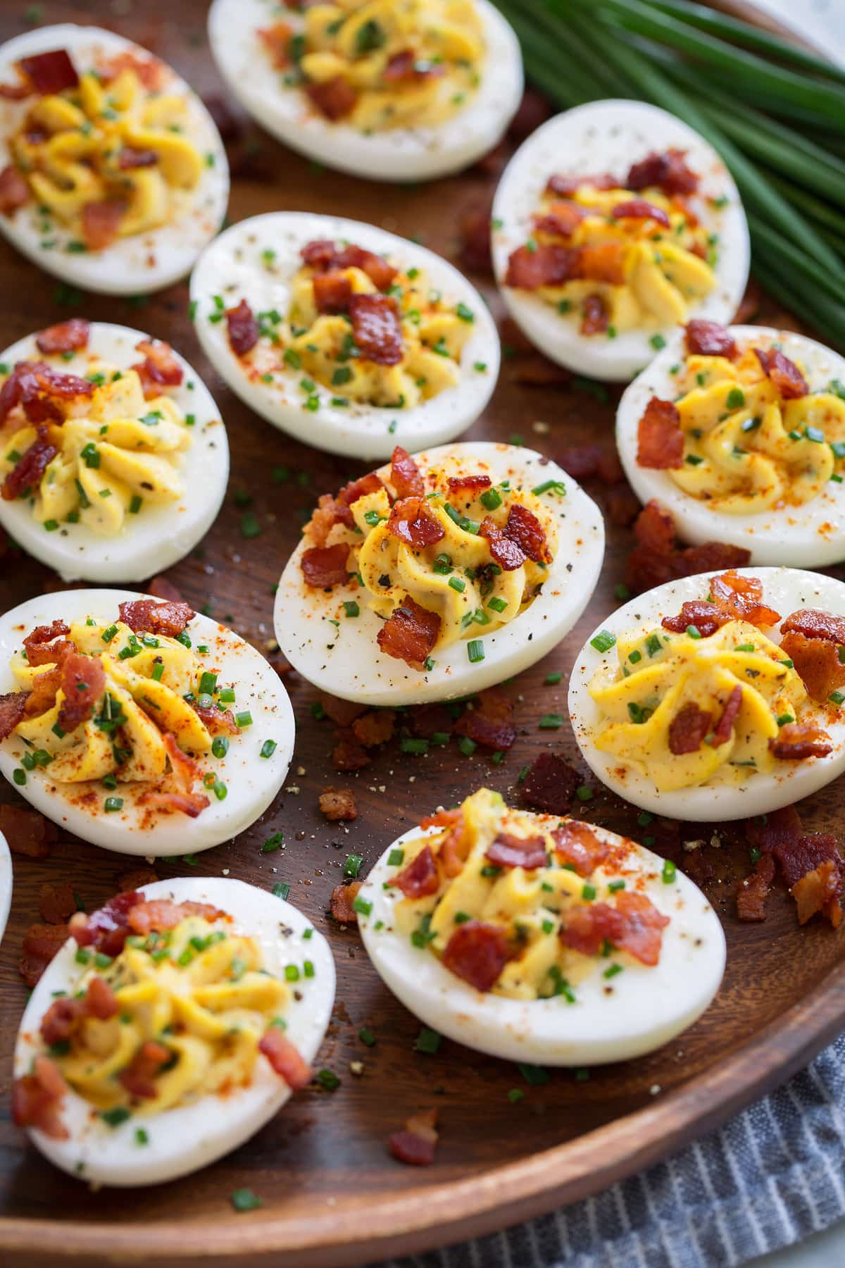 Wooden plate filled with deviled eggs. Eggs filled with a creamy mayonnaise and egg yolk filling and are garnished with chives and bacon.