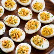 Deviled eggs on a wooden serving platter.