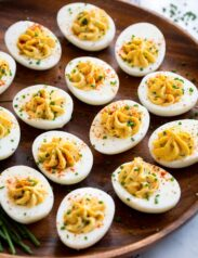Deviled eggs on a wooden serving platter.