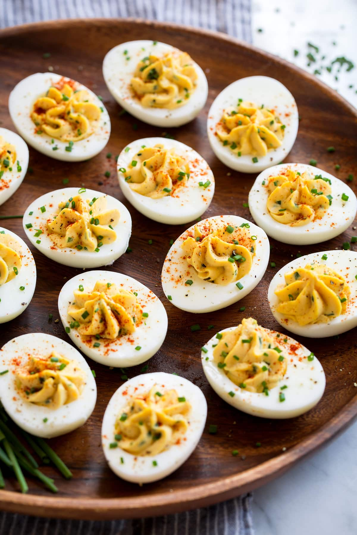 Plain deviled eggs on a wooden platter (no bacon).