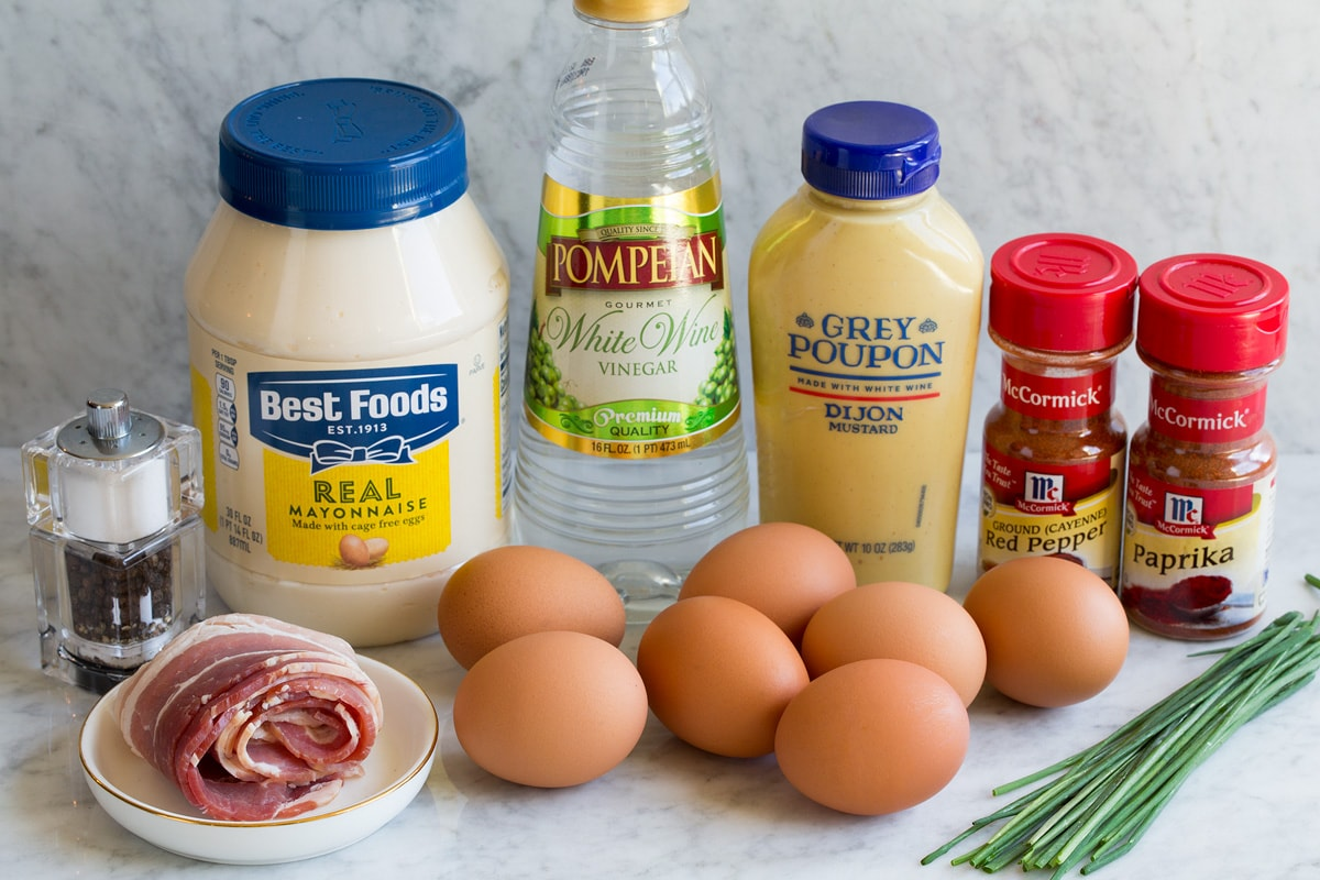 Image showing ingredients that go into deviled eggs including mayonnaise, dijon mustard, white wine vinegar, eggs, chives, cayenne pepper, paprika, chives and bacon.