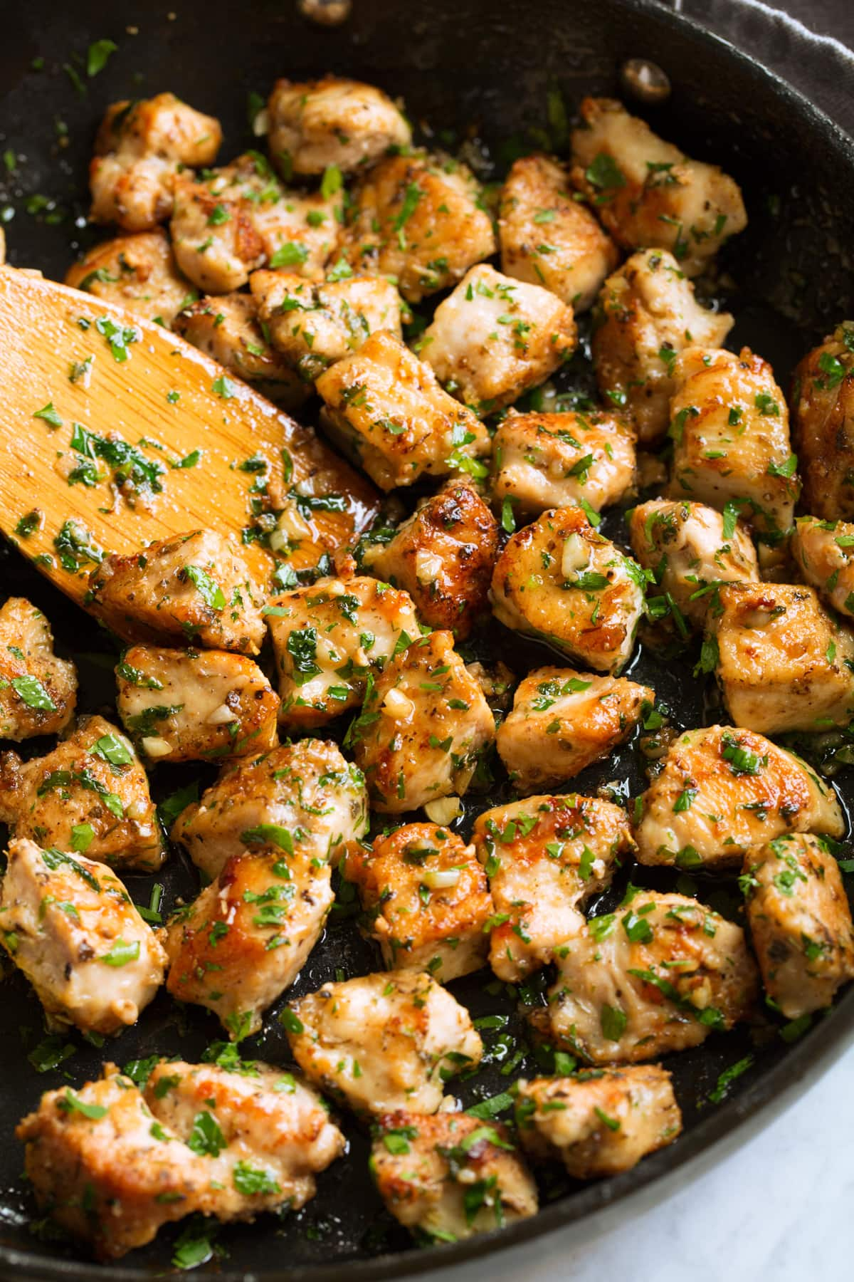 Chicken bites in a skillet with garlic and butter sauce.