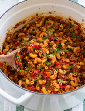Goulash with macaroni, ground beef, and vegetables in a white pot.
