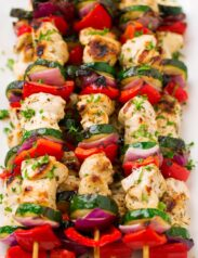 Greek Chicken Kebabs on skewers with marinated chicken breast, zucchini, bell pepper and red onion.