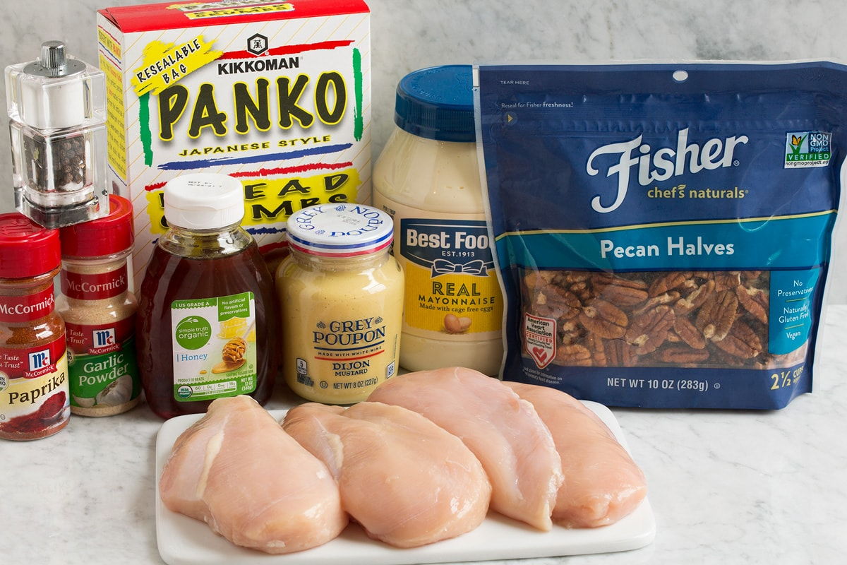 Image of ingredients used to make honey mustard pecan chicken. Shows pecans, chicken breasts, mayonnaise, dijon mustard, panko, paprika, garlic powder, honey, salt and pepper.