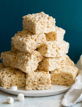Stack of cut rice krispie treats on a platter.