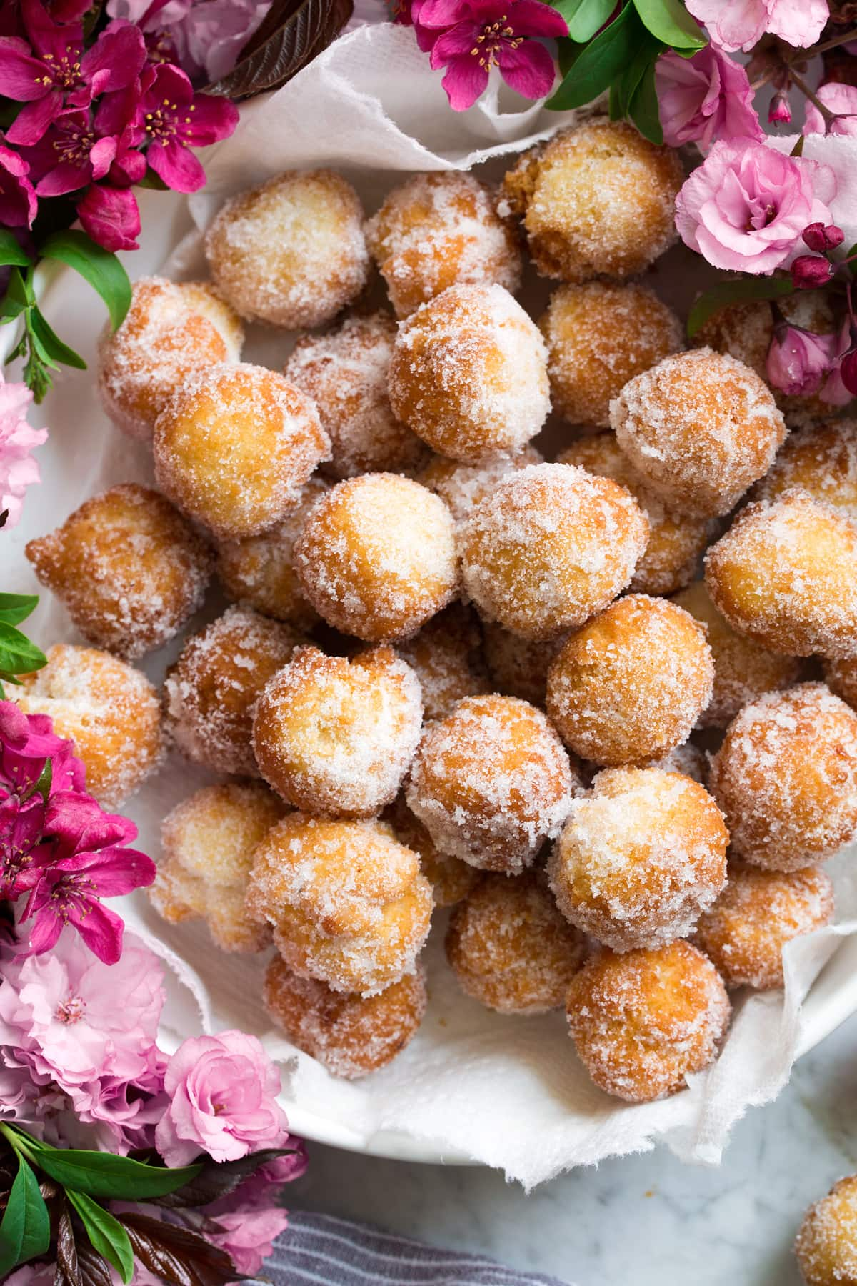 Bowl full of fresh donut holes covered in cinnamon sugar.