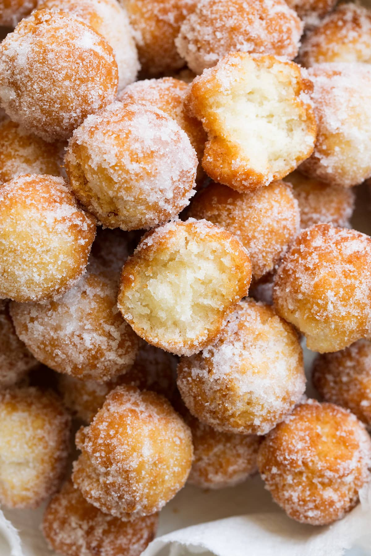 Close up image of donut holes coated in cinnamon sugar.