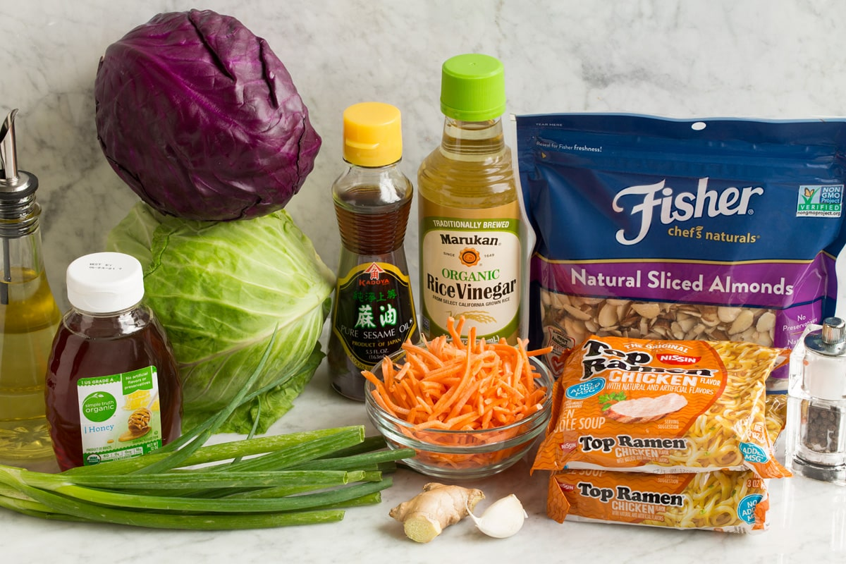 Ingredients used to make Asian ramen noodle salad shown in this image. Includes red and green cabbage, carrots, almonds, dry ramen noodles, honey, rice vinegar, sesame oil, garlic, ginger and oil.