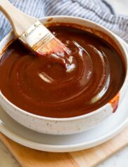 Bowl of bbq sauce with a basting brush resting in the sauce.
