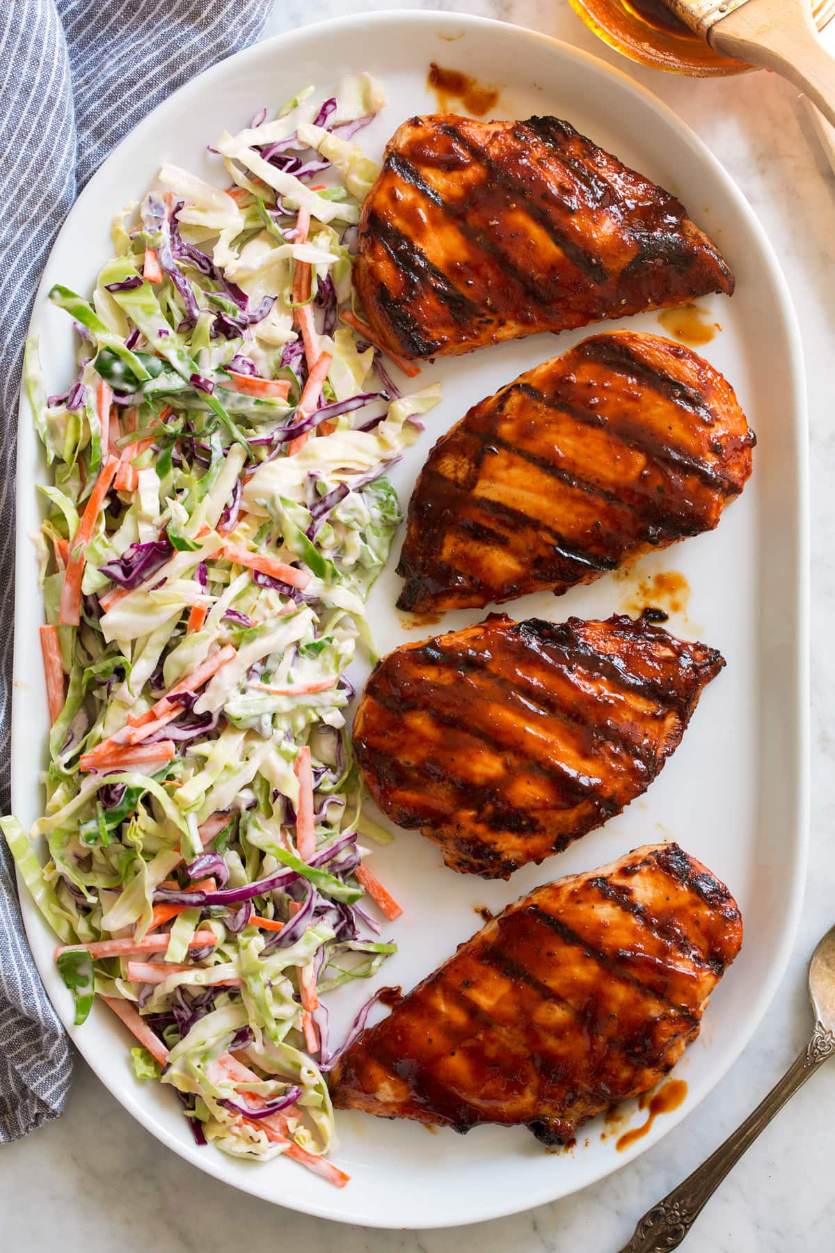 Overhead image of four grilled chicken breasts covered in bbq sauce on a platter with a side of coleslaw on the side of the platter.