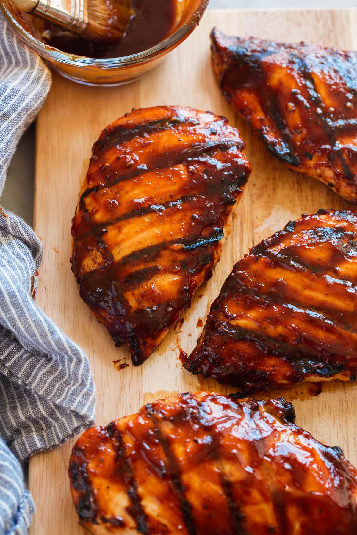 Grilled chicken breasts covered in bbq sauce on a wooden cutting board.