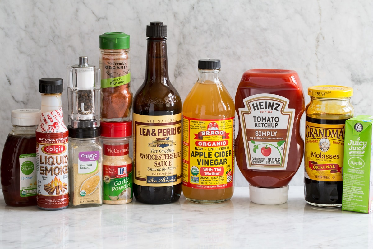 Image of ingredients used to make homemade bbq sauce shown. Including honey, liquid smoke flavor, dry mustard, salt and pepper, garlic powder, smoked paprika, Worcestershire, apple cider vinegar, ketchup, molasses and apple juice.