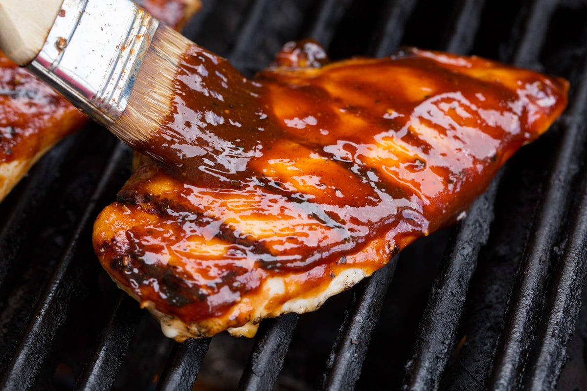 Basting chicken breast on grill with bbq sauce.