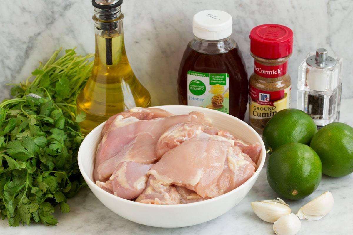 Image of ingredients used to make cilantro lime chicken shown here. Including chicken thighs, cilantro, limes, garlic, cumin, honey, olive oil, salt and pepper.