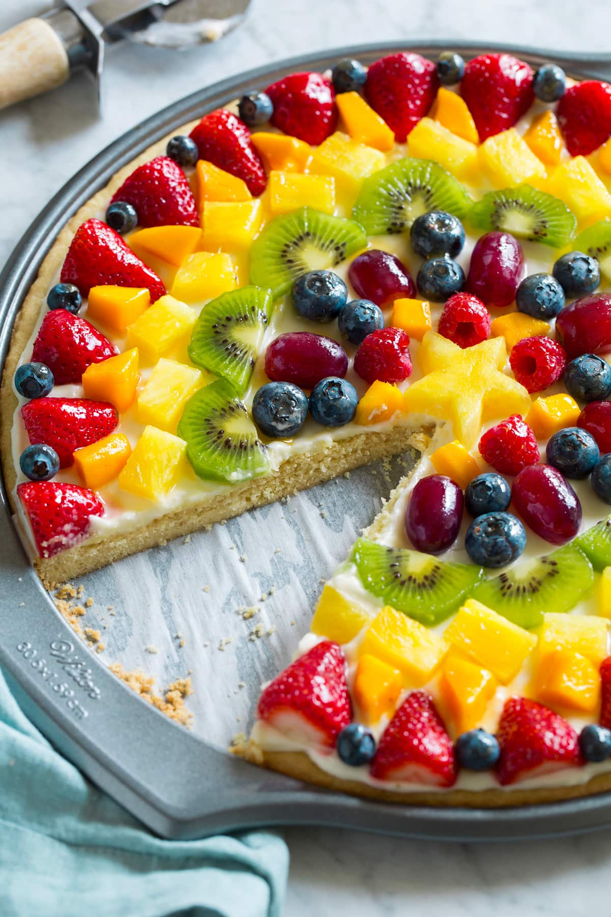Side view of fruit pizza with one slice removed to show texture of interior.