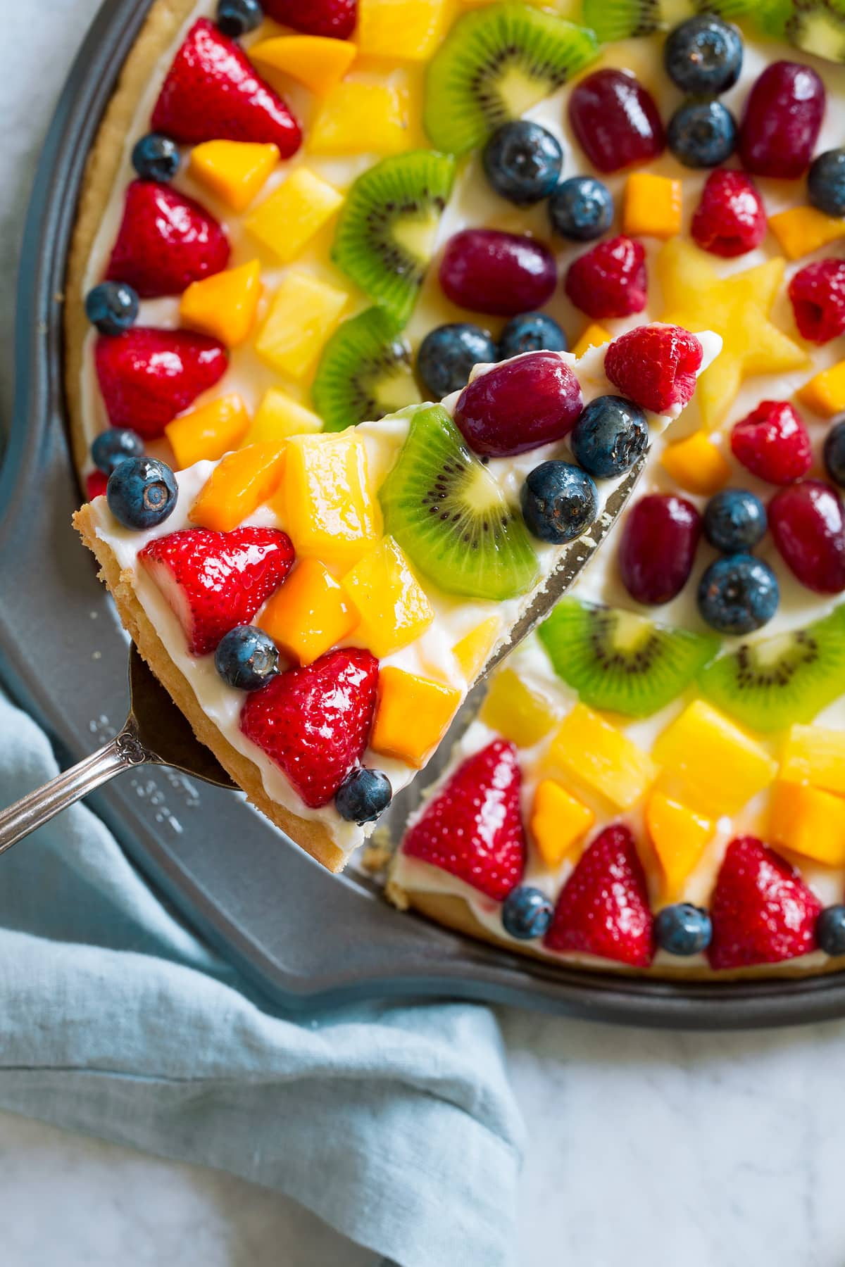 Overhead image of fruit pizza with slice cut and lifted out.