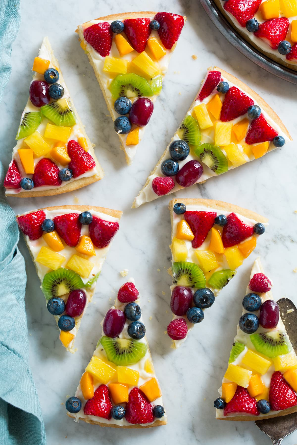 Slices of fruit pizza on a marble surface.