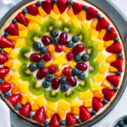 Homemade fruit pizza decorated in a artistic pattern with colorful fresh fruit.
