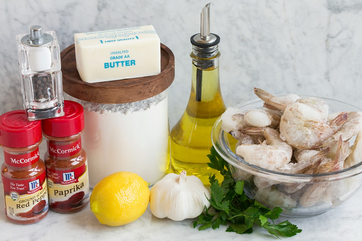 Image of ingredients used to make Hawaiian garlic shrimp. Includes raw shrimp, olive oil, parsley, garlic, lemon, flour, butter, paprika, cayenne pepper, salt and pepper.