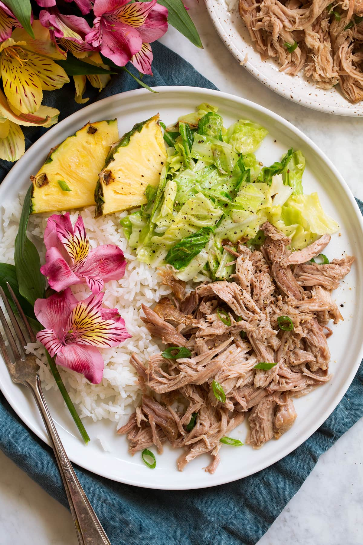Single serving of shredded kalua pork on a white serving plate shown with sides of white rice, sautéed cabbage, fresh pineapple and flowers.