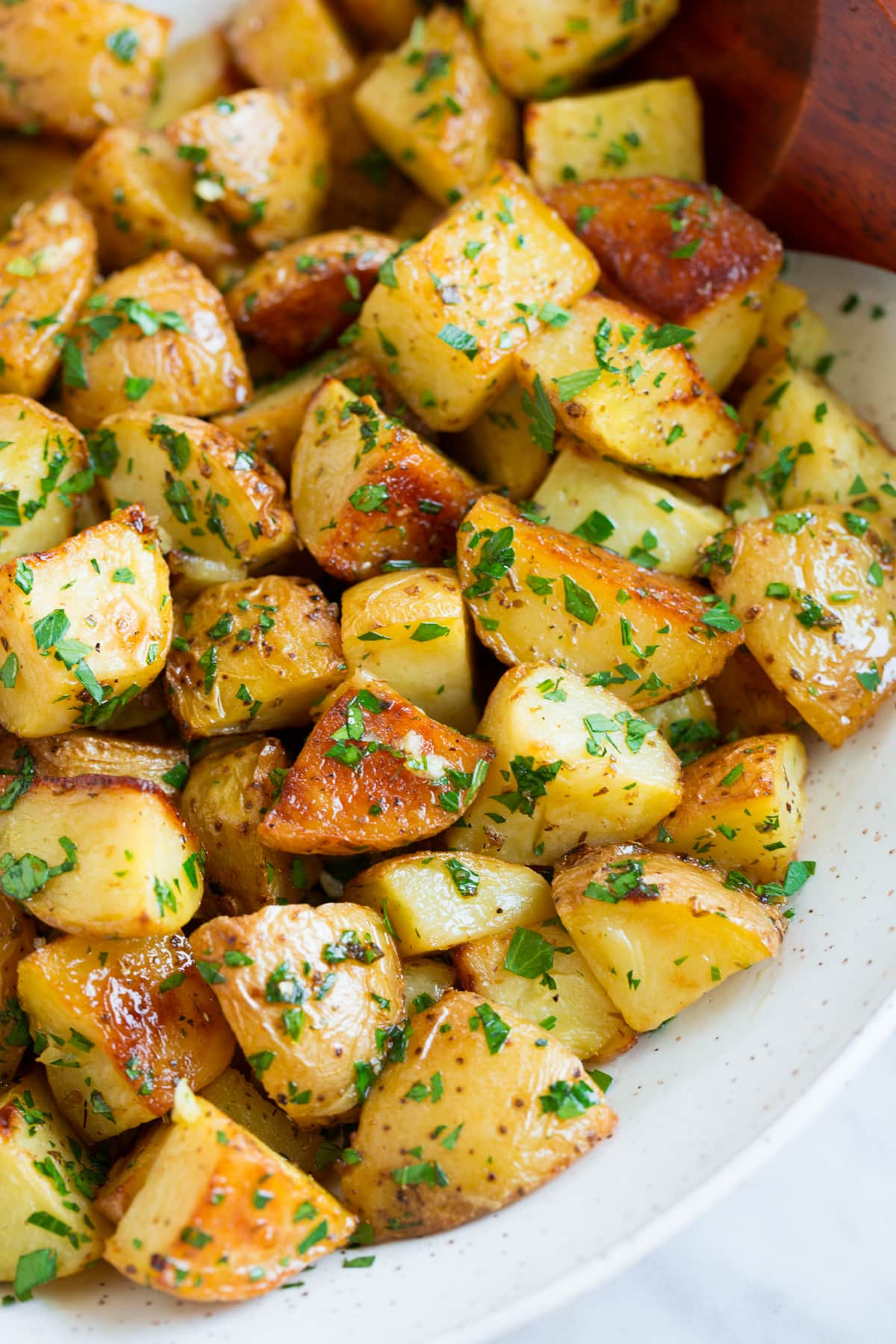 Close up image of roasted potatoes with lemon and parsley in a white serving bowl.