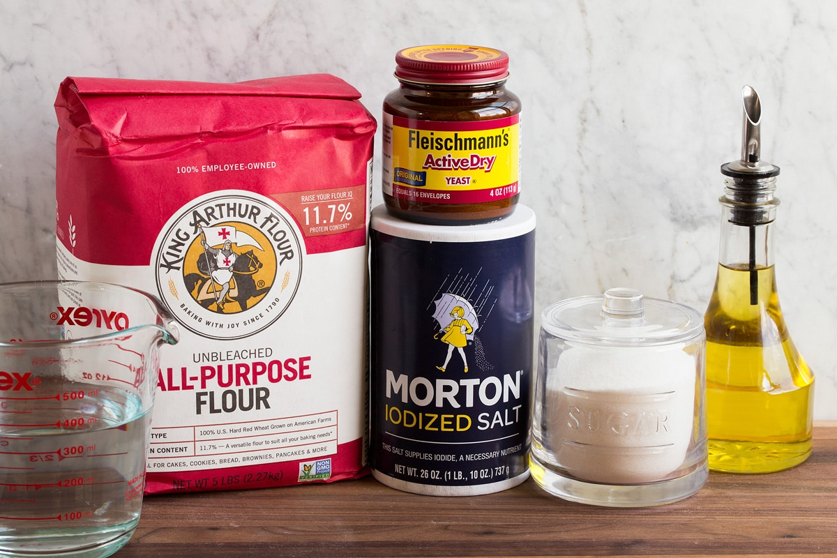 Image of ingredients used to make pizza dough. Includes all-purpose flour, water, salt, yeast, sugar and olive oil.