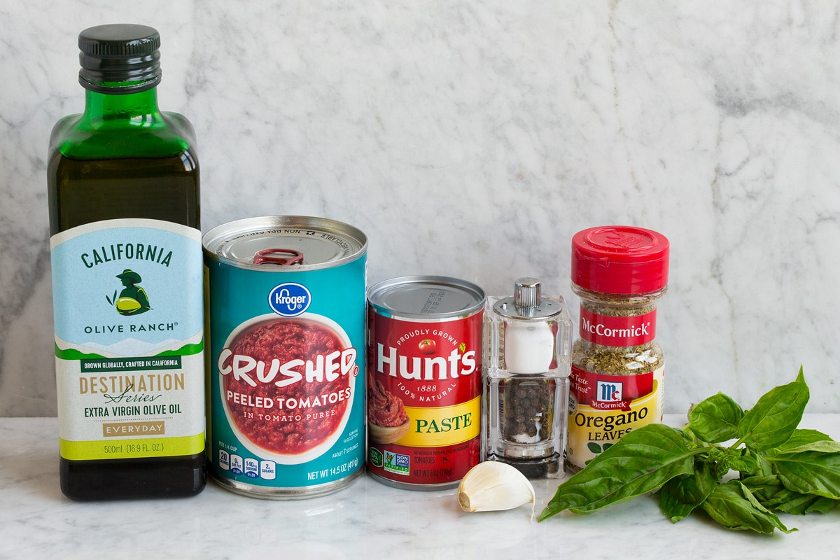 Ingredients used to make shown including olive oil, crushed tomatoes, tomato paste, salt and pepper, dried oregano, fresh basil, garlic, salt and pepper.