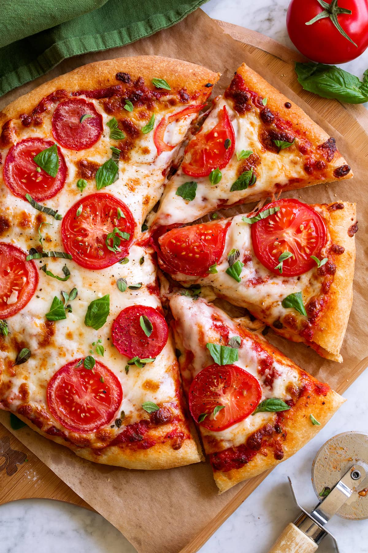 Pizza topped with red pizza sauce, mozzrella, tomatoes and herbs. It is cut into slices and sitting on parchment paper over a wooden pizza peel.
