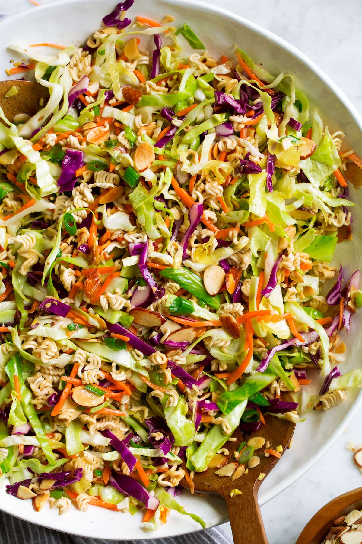 Close up overhead image of Asian ramen noodle salad in a large white salad bowl set over a marble surface.