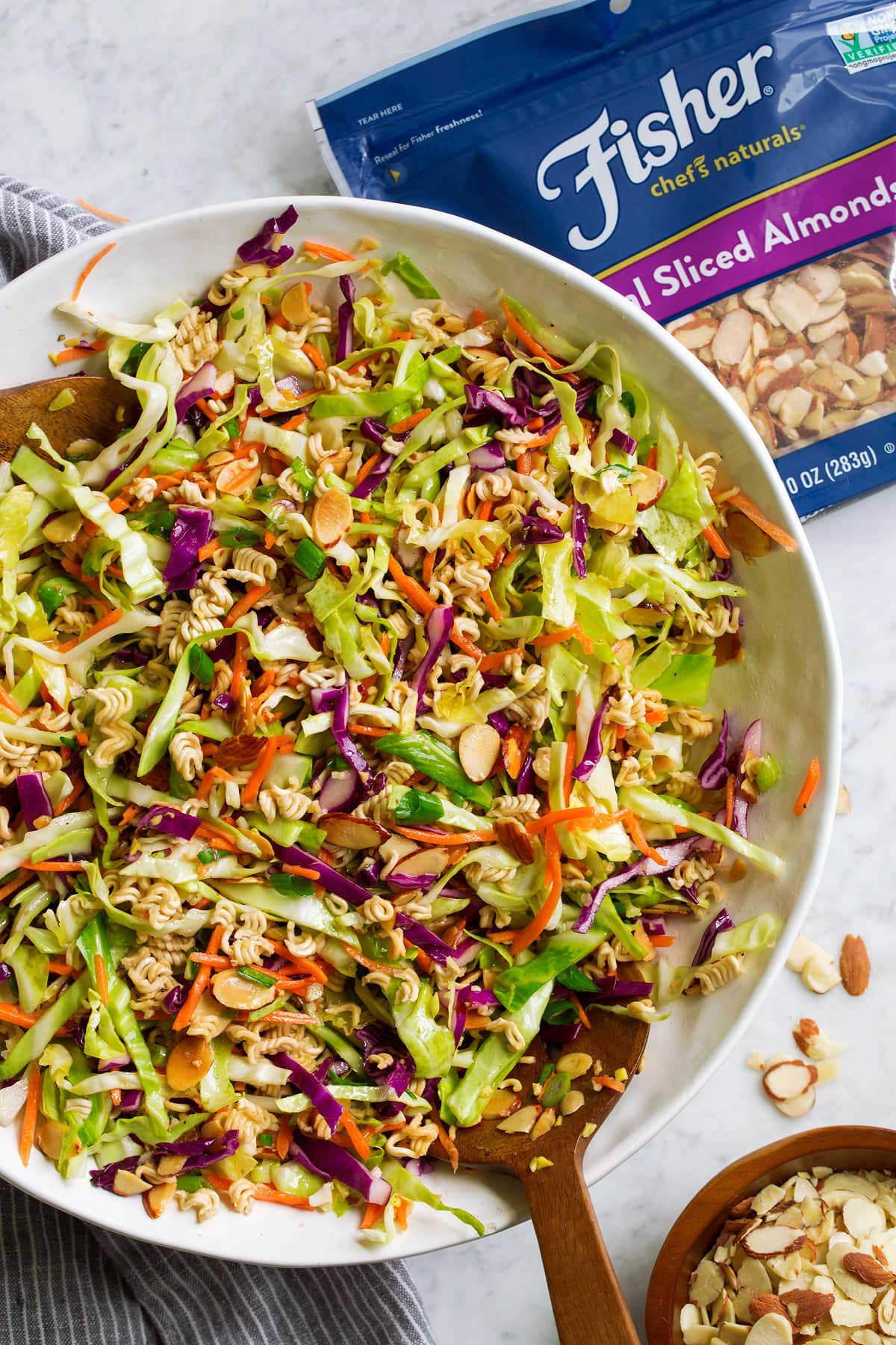 Overhead image of ramen noodle salad tossed together in a large white bowl.