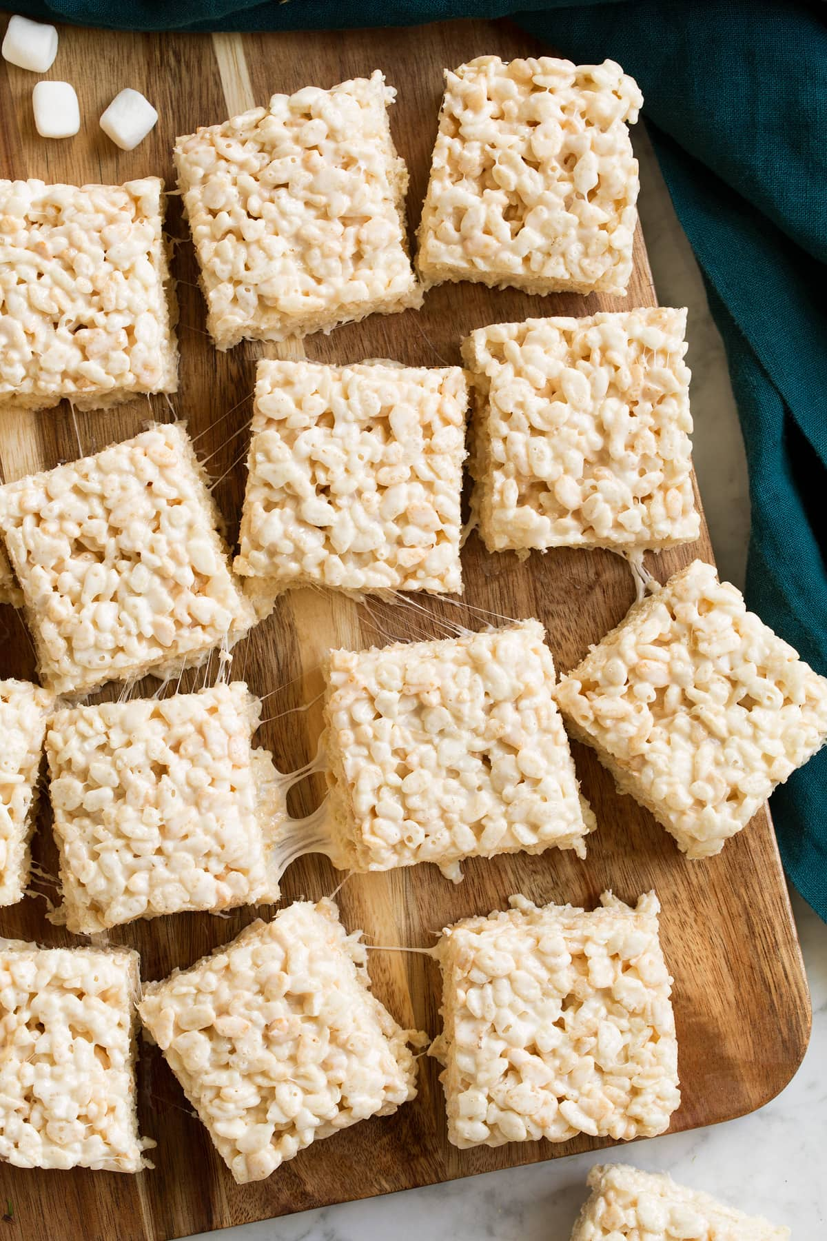 Overhead image of rice krispie treat squares on a wooden cutting board.