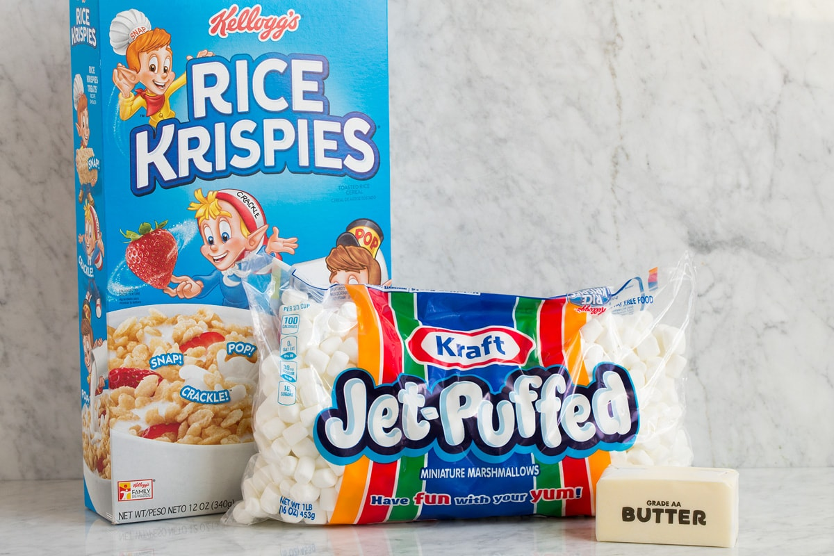 Image of three ingredients needed to make rice krispie treats shown here. Includes rice krispies cereal, mini marshmallows and butter.