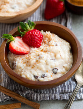 Rice Pudding in a small wooden bowl. It is garnished with cinnamon and strawberries.