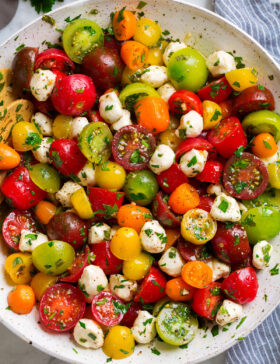 Tomato Salad in a white serving bowl. Shown in salad are multi-color cherry tomatoes and grape tomatoes, mozzarella pearls and it's coated in a herb dressing.