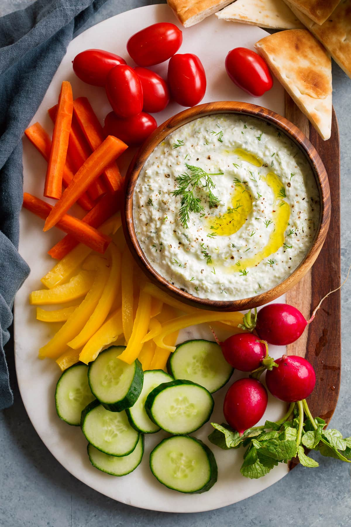 Overhead image of tzatziki sauce dip on a marble platter with fresh vegetables around it.