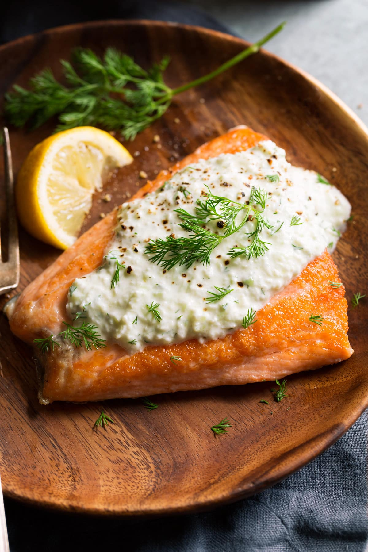 Showing serving suggestion pairing tzatziki sauce atop a salmon fillet.