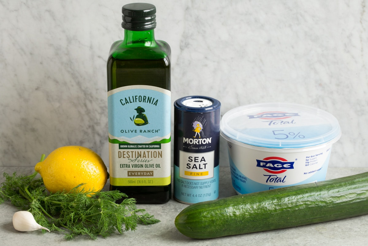 Image of ingredients used to make tzatziki sauces. Includes Greek yogurt, cucumber, salt, lemon, olive oil, dill and garlic.