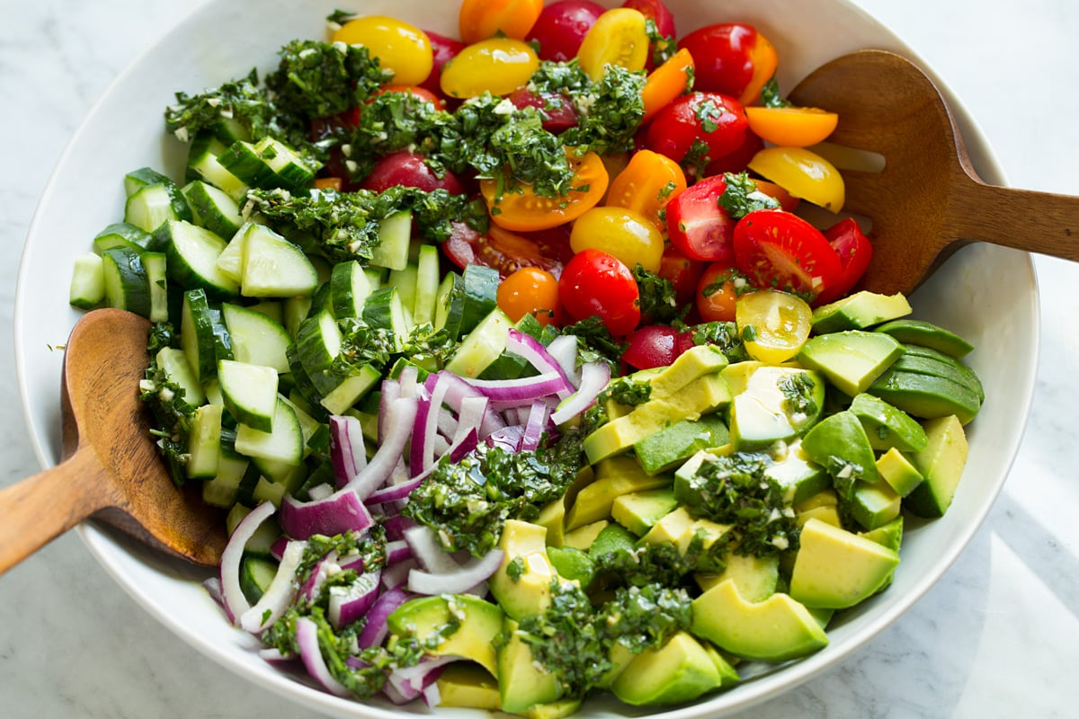Avocado salad in a mixing bowl shown before tossing with dressing.