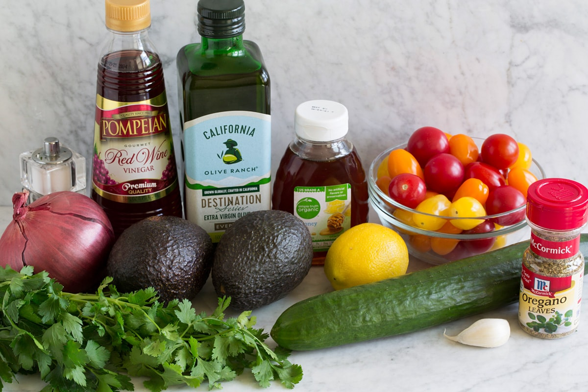 Image of ingredients that go into avocado salad. Includes fresh avocados, red onio, cilantro, parsley, cucumber, garlic, lemons, grape tomatoes, honey, olive oil, red wine vinegar and oregano.