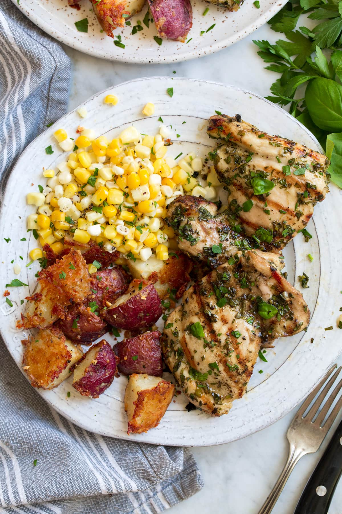 Overhead image of garlic and herb marinated grilled chicken thighs with corn and roasted red potatoes as sides. Food is resting on a white plate set over a marble surface.