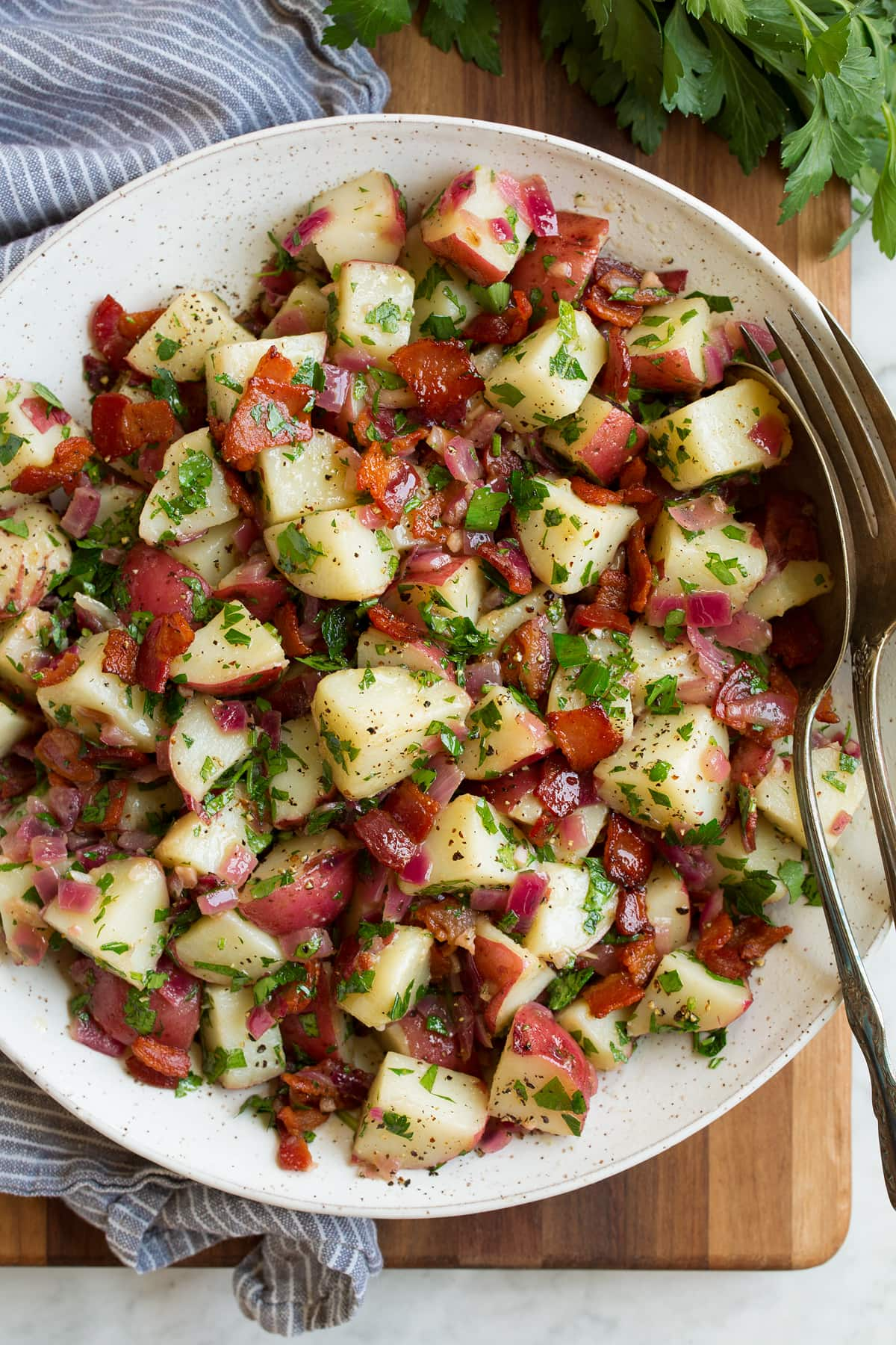 Overhead image of german potato salad in a bowl with a grey striped napkin to the side.