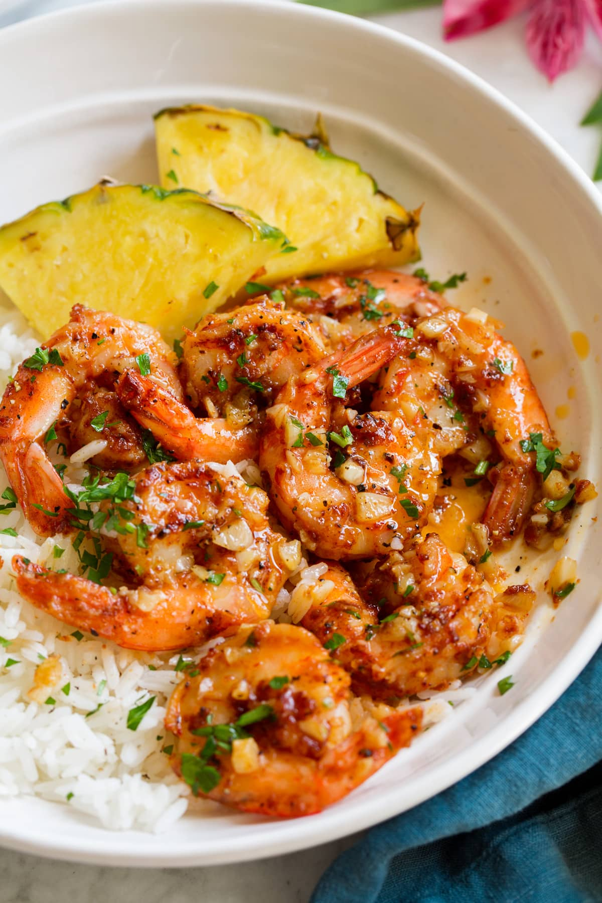 Close up image of Hawaiian garlic shrimp served over white rice with slices of fresh pineapple.