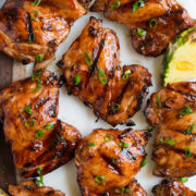 Close up image of huli huli chicken thighs on a platter. Shown overhead.