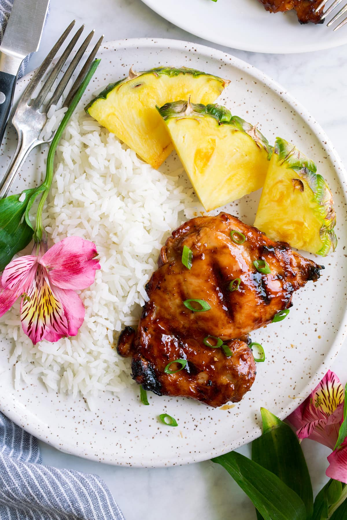 Plate with 1 huli huli chicken piece, pineapple, rice and a fresh flower. Shown overhead.