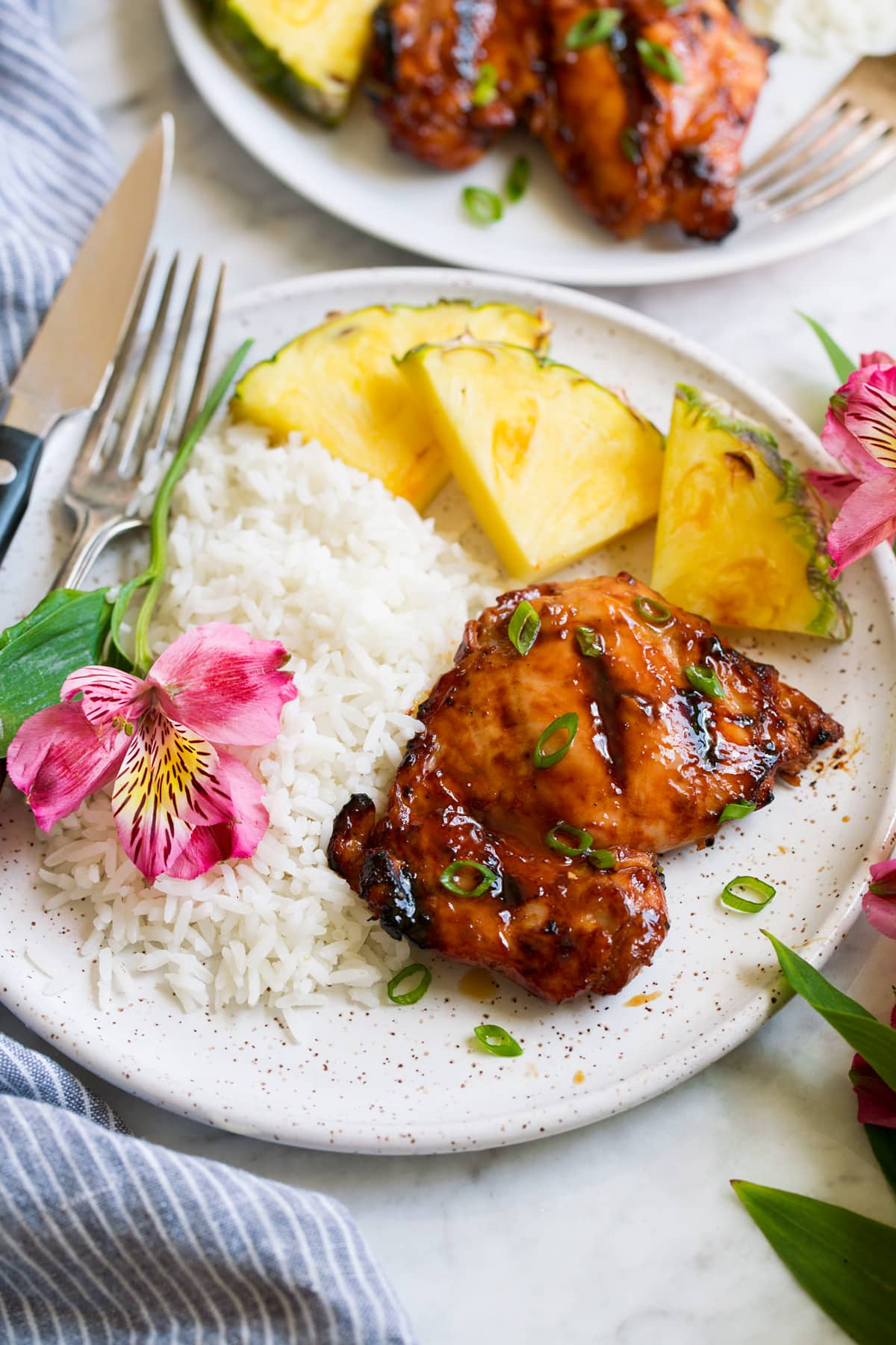 Plate with 1 huli huli chicken piece, pineapple, rice and a fresh flower. Shown from the side.