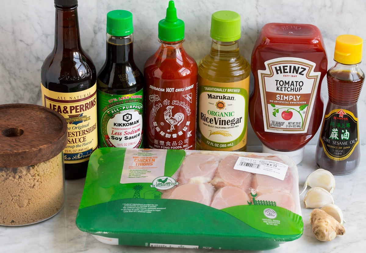 Image of ingredients used to make hawaiian huli huli chicken. Includes chicken thighs, brown sugar, Worcestershire sauce, soy sauce, sriracha, rice vinegar, ketchup, sesame oil, ginger and garlic.