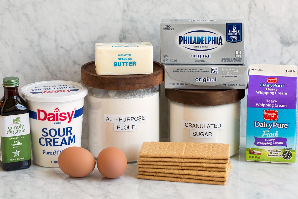 Image of ingredients used to make mini cheesecakes. Includes cream cheese, granulated sugar, all-purpose flour, eggs, graham crackers, sour cream, heavy cream, vanilla and butter.