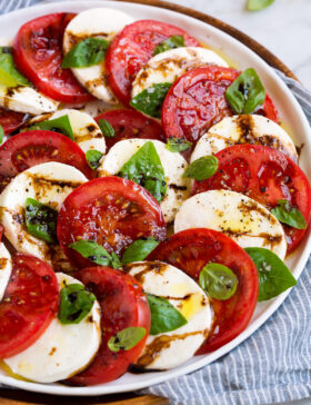 Caprese salad layered in a pretty design shown on a white platter.