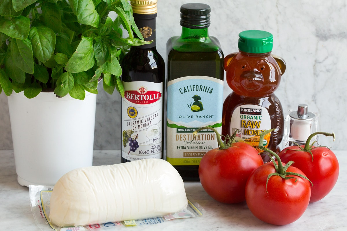 Caprese Salad Ingredients shown in this image. Includes fresh mozzarella, fresh basil, fresh tomatoes, olive oil, honey, balsamic vinegar, salt and pepper.